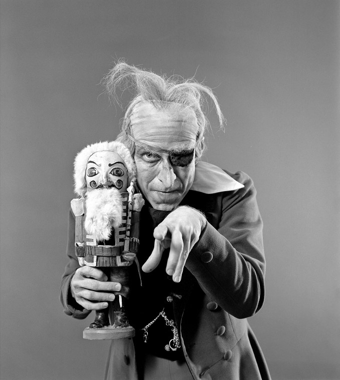 A man in old-age makeup wears an eye patch, thinning tufts of hair, holds a Nutcracker toy, and points at the camera