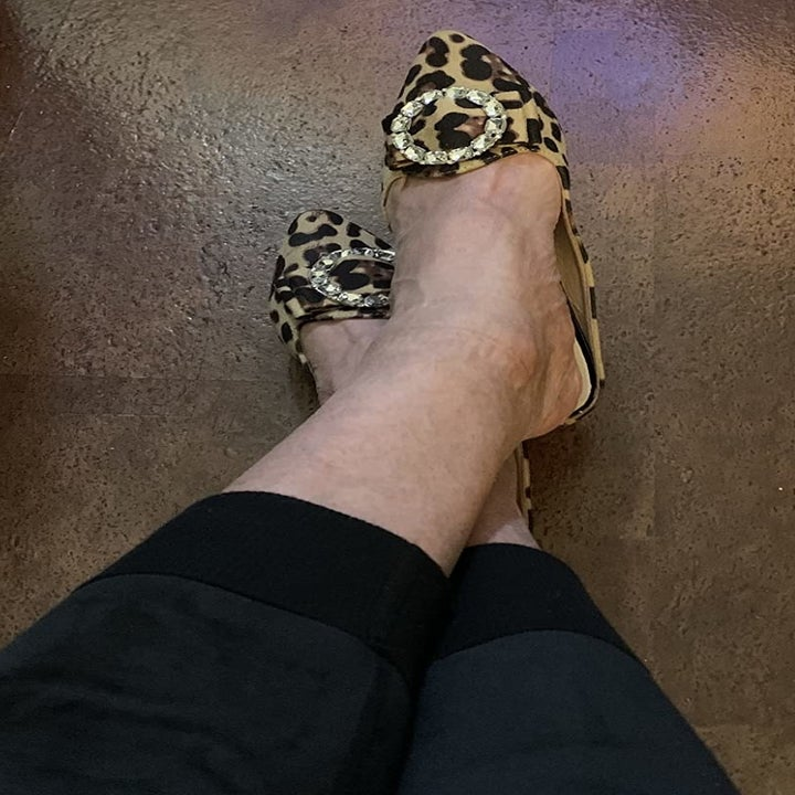 A reviewer wearing the shoes in leopard