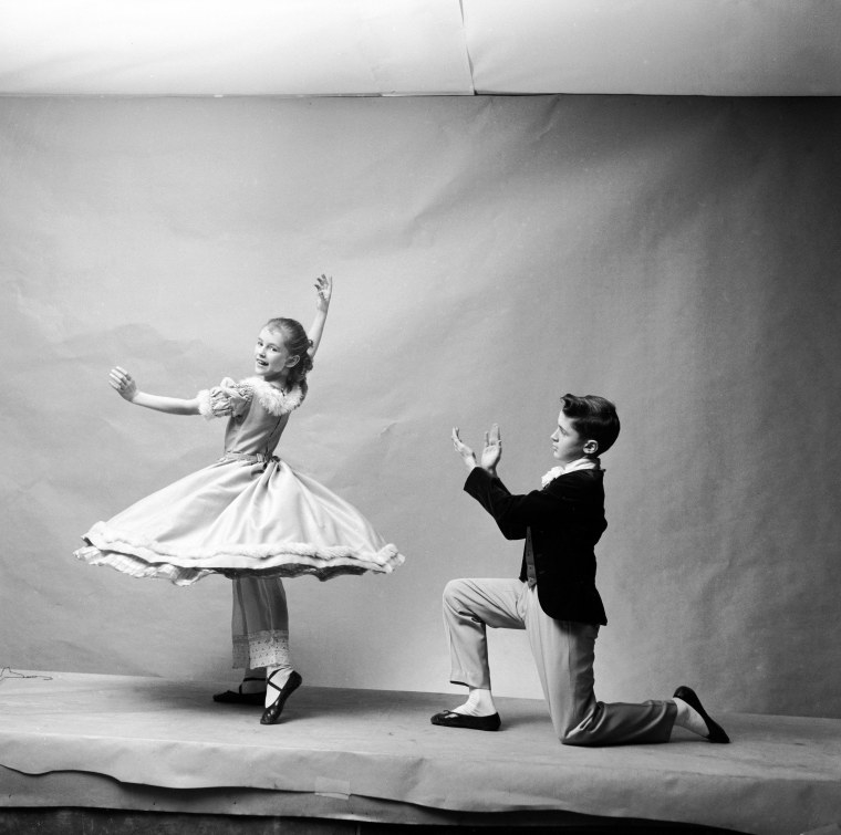 A girl ina dress twirls and a boy kneels and claps beside her in a studio photo shoot