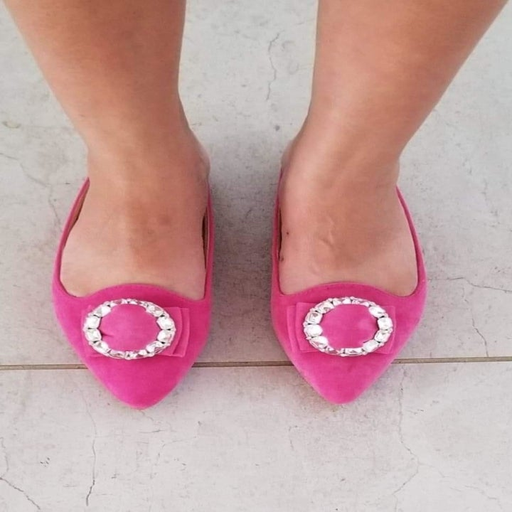 A reviewer wearing the hot pink pointed toe slides with a rhinestone buckle