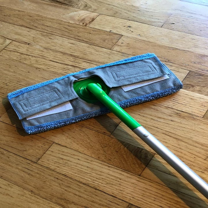 A reviewer photo of the reusable microfiber pad on a standard Swiffer Sweeper