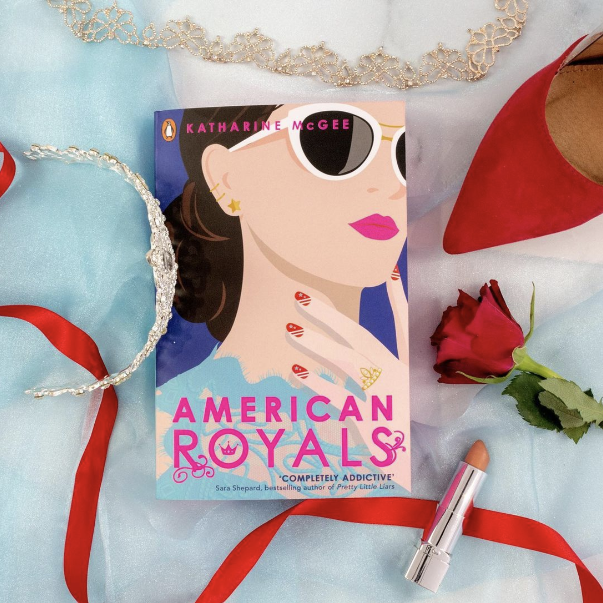 the book on a table surrounded by a crown, lipstick, a rose, and a shoe