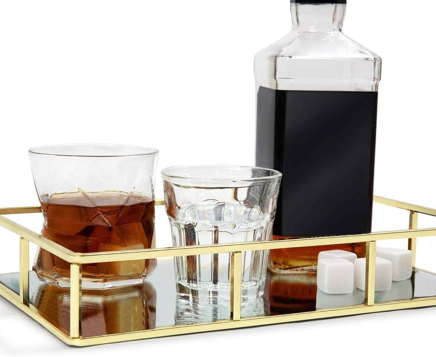 The vanity tray with glassware and a bottle of alcohol sitting on it