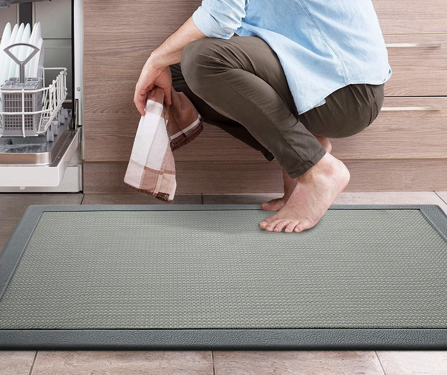 A person crouching on the anti-fatigue mat