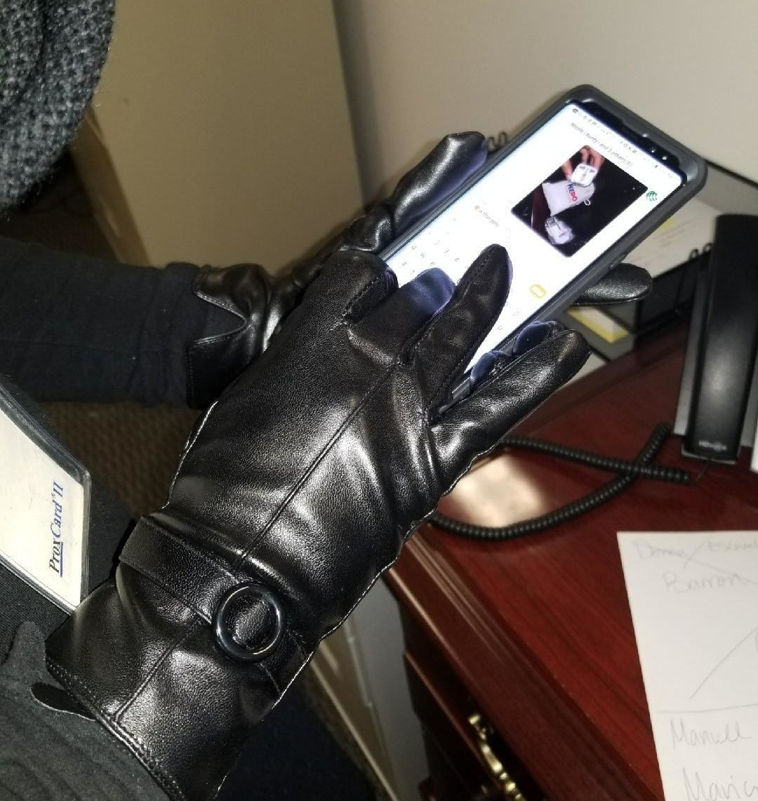 reviewer photo showing person texting while wearing the touchscreen leather gloves in black