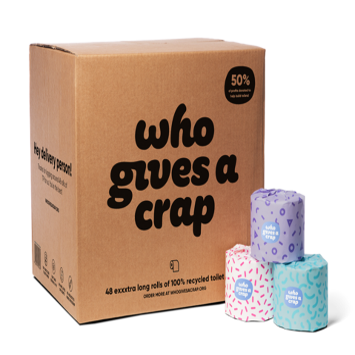 """A cardboard box that says """"who gives a crap"""" next to a small pyramid of toilet paper"""