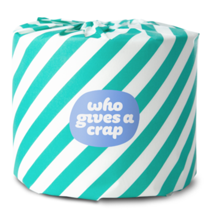 """A roll of toilet paper wrapped in paper printed with teal and white stripes with a small badge that says """"who gives a crap"""""""