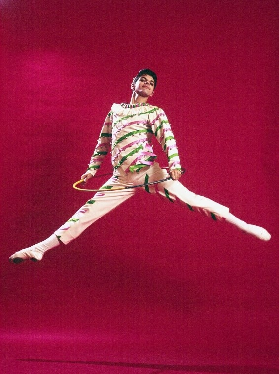A boy in a candy cane outfit leaping in the air
