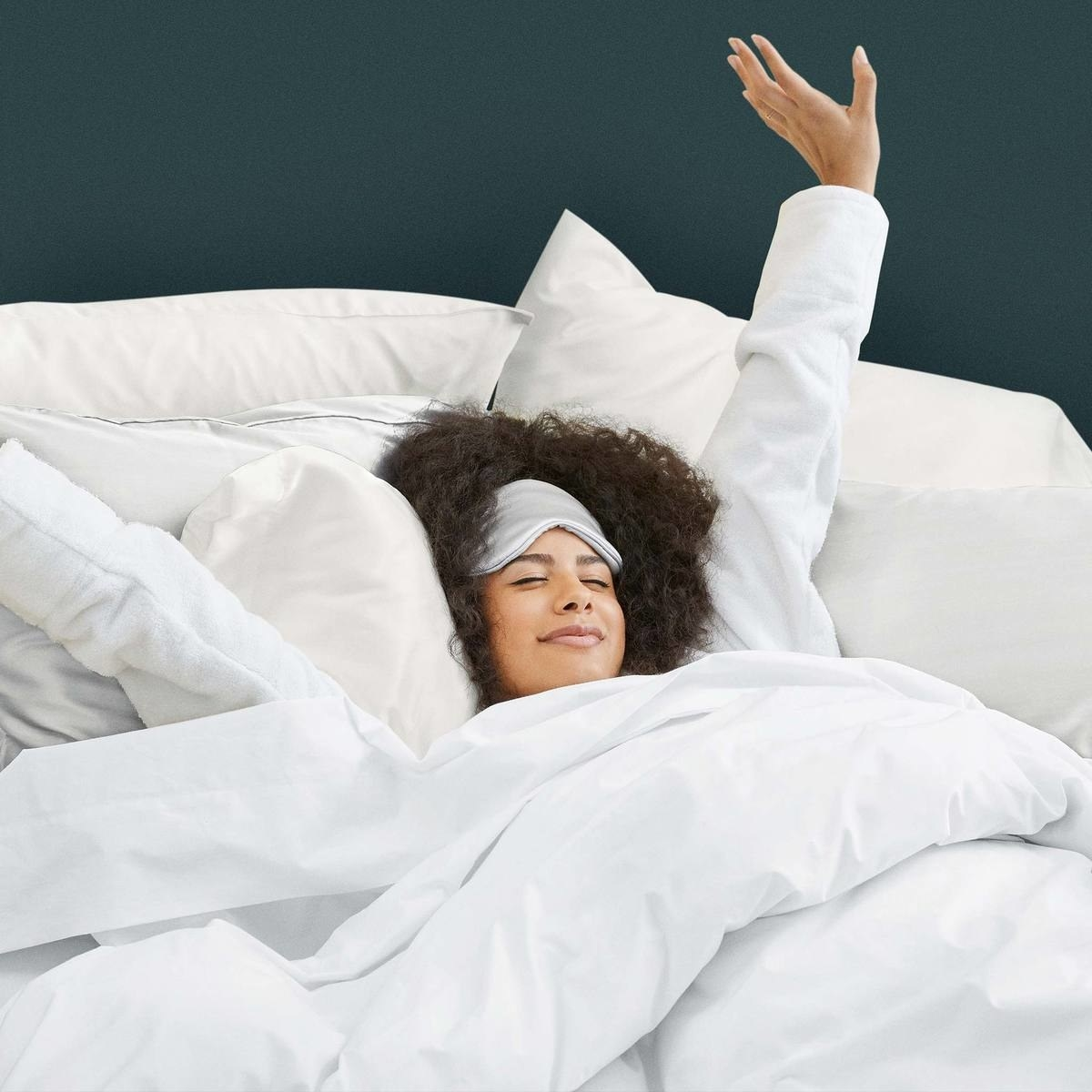 a model stretches from under brooklinen bedding