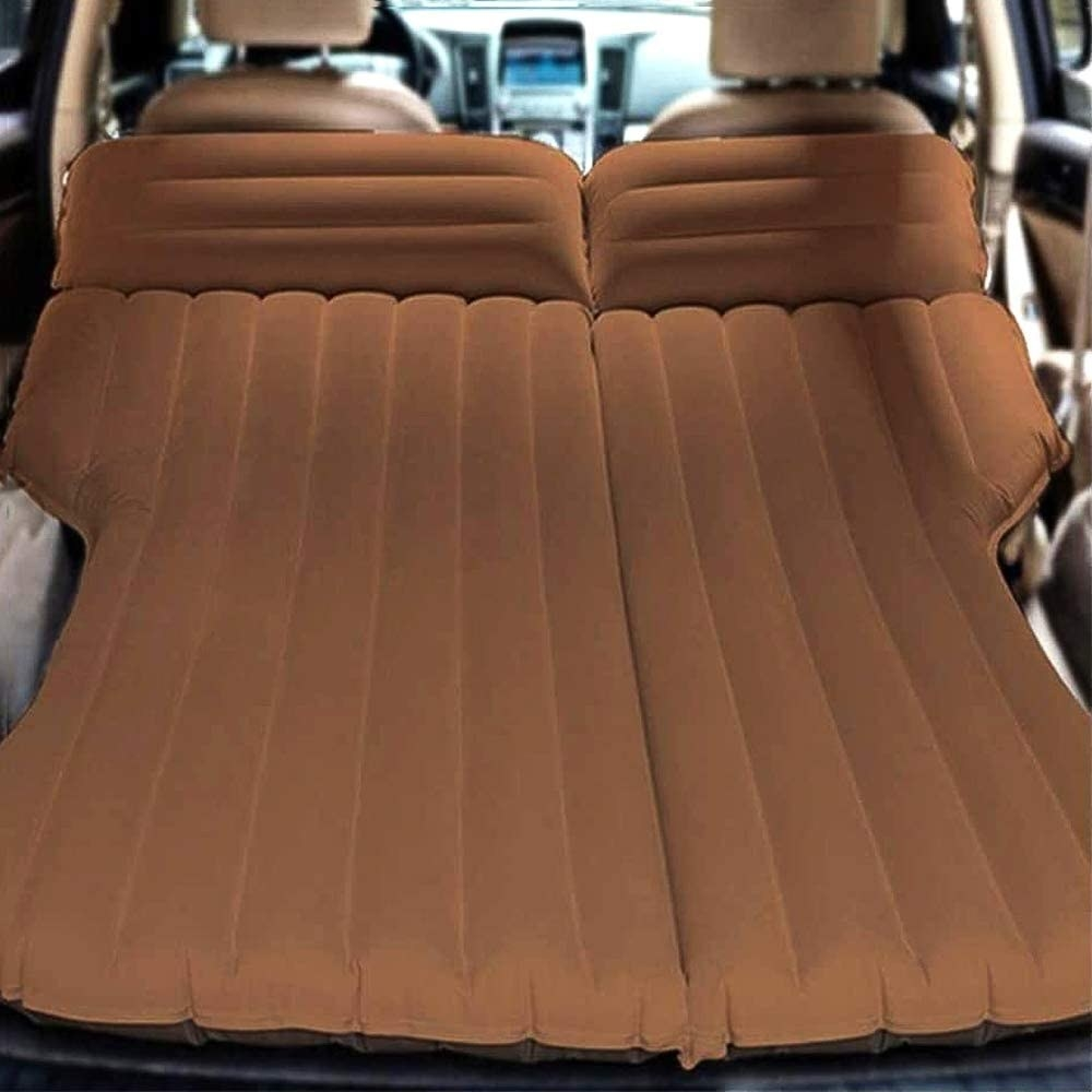 A large inflatable car mattress tucked into the trunk and back seat of a car
