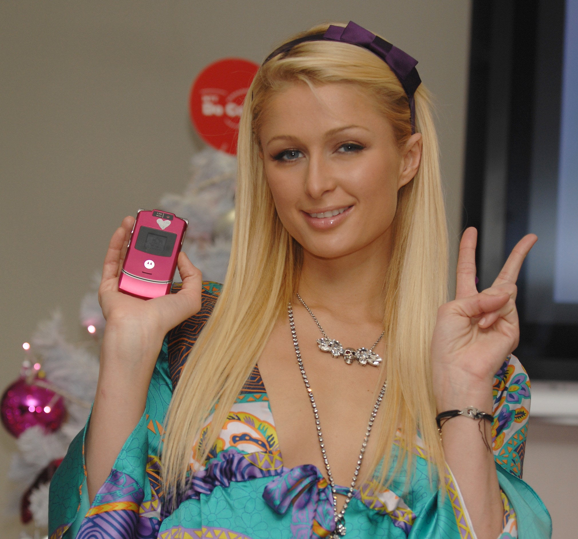 Paris Hilton holds up a pink Motorola Razr as she gives a peace sign
