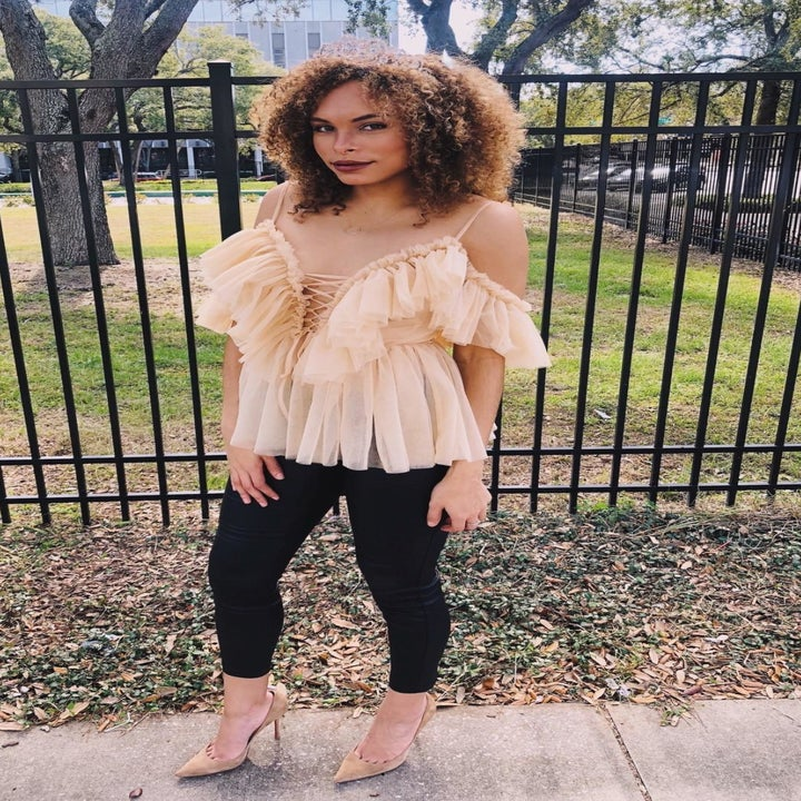 A reviewer wearing the tan cold shoulder tulle ruffle top with short sleeves, spaghetti straps, and a lace-up detail in the front