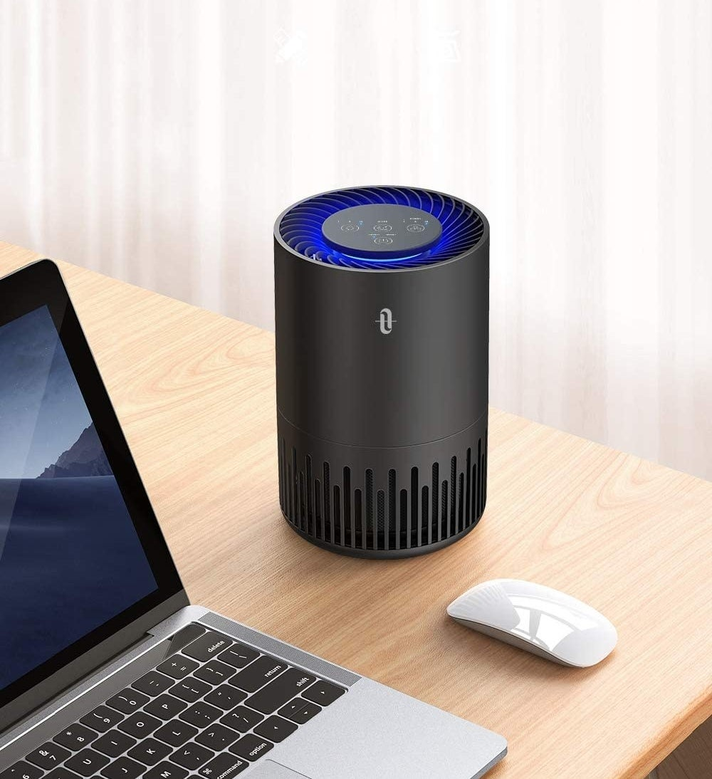 The air purifier perched on a desk next to a laptop and wireless mouse