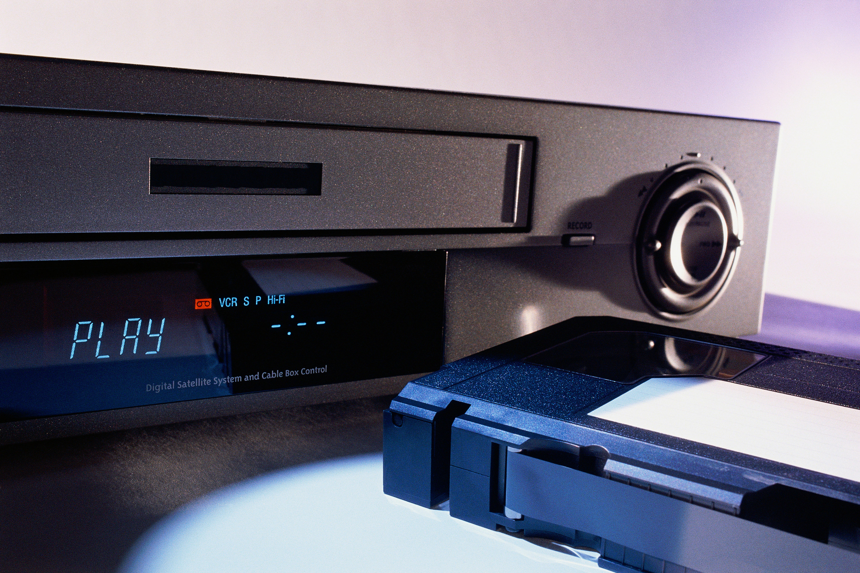 A VCR next to a VHS tape