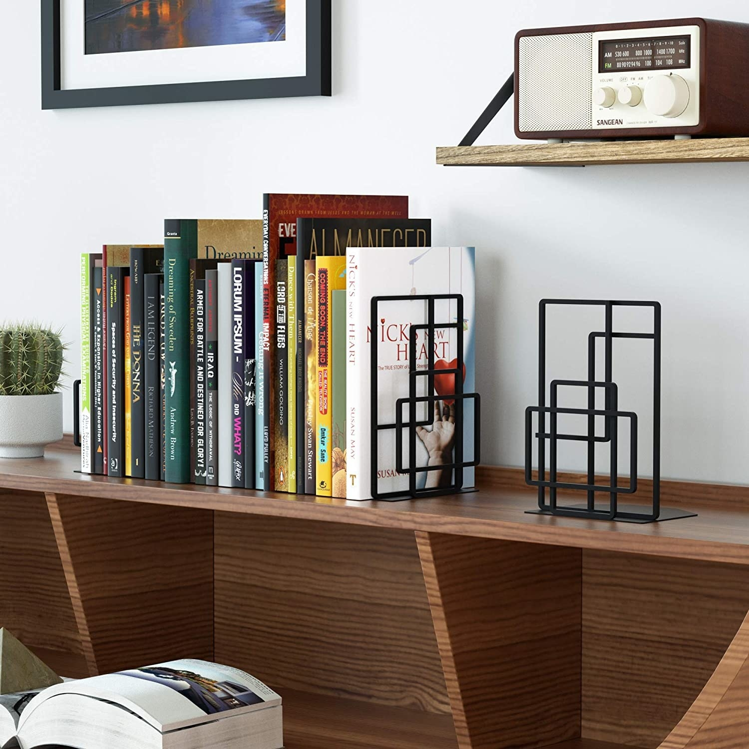A pair of geometric metal bookends keeping a stack of books upright on a shelf