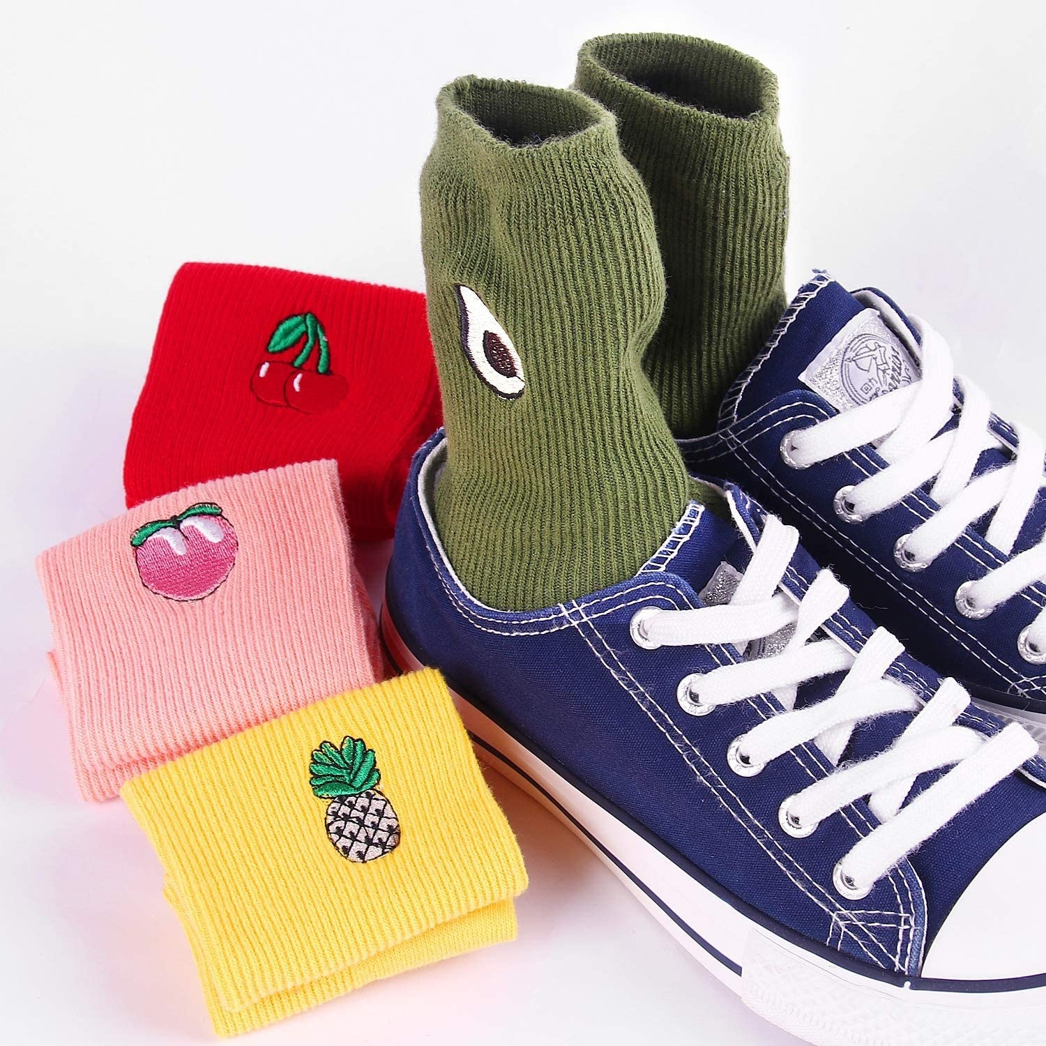The socks with embroidered fruit on the ankles: green with avocados, red with cherries, pink with peaches, and yellow with pineapples