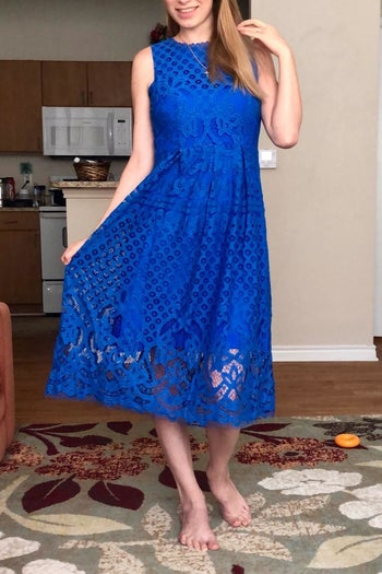 A reviewer wearing the fit and flare lace dress in royal blue