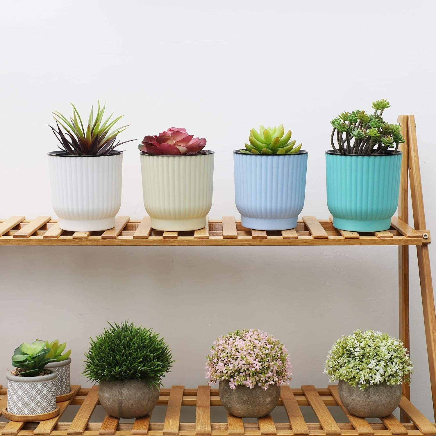 A set of four self-watering planters arranged side by side on a bamboo shelf