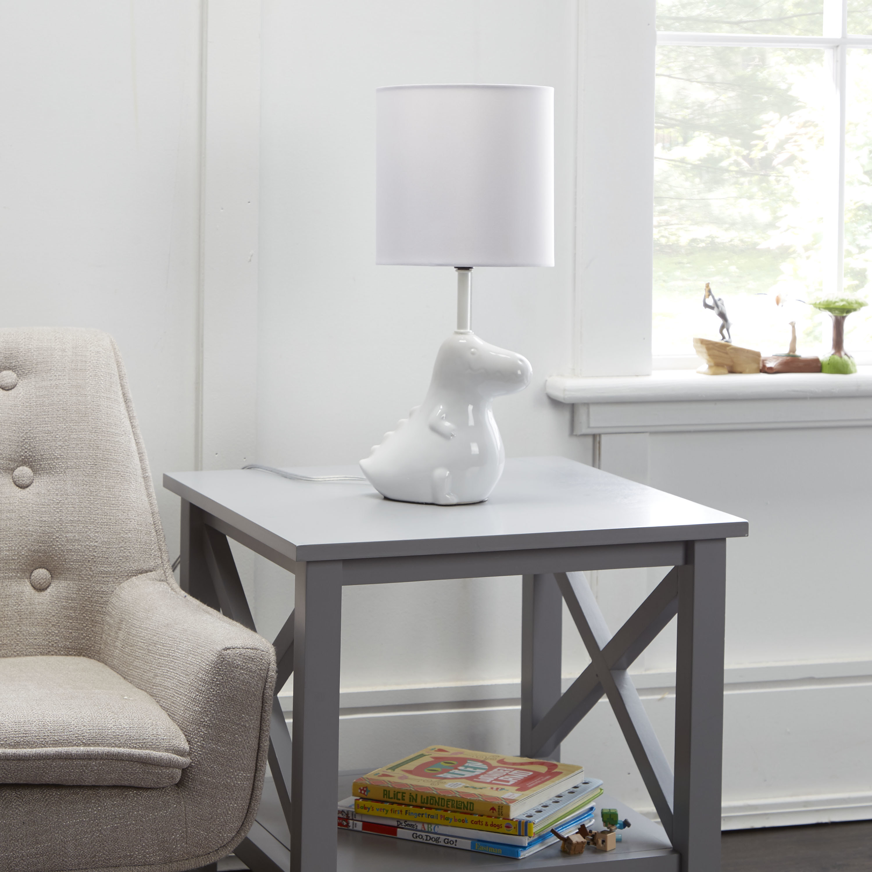 The white dinosaur lamp on an end table