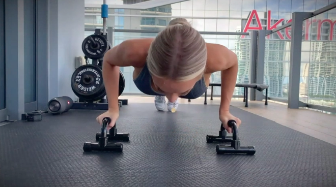 Model goes down in push-up position while holding black push-up handle bars on floor