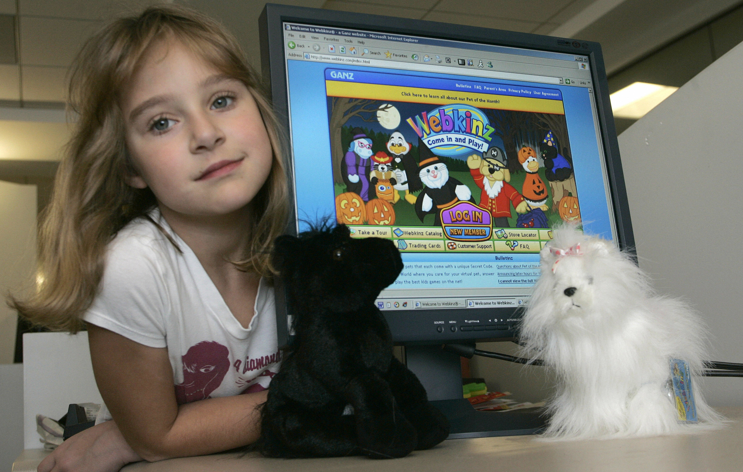 A young girl poses next to a computer showing the Webkinz website and two stuffed Webkinz