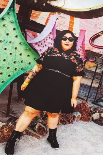 A reviewer wearing the black short sleeve dress with an embroidered floral sheer panel at the chest with a belt