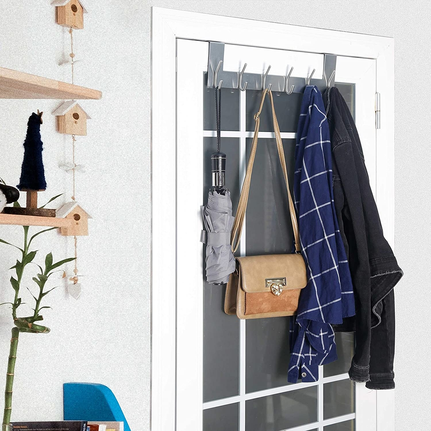 An over the door hook holding an umbrella, a purse, and two jackets