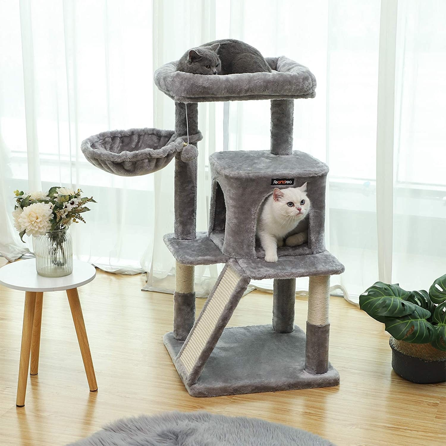 A pair of cats playing in a large cat condo