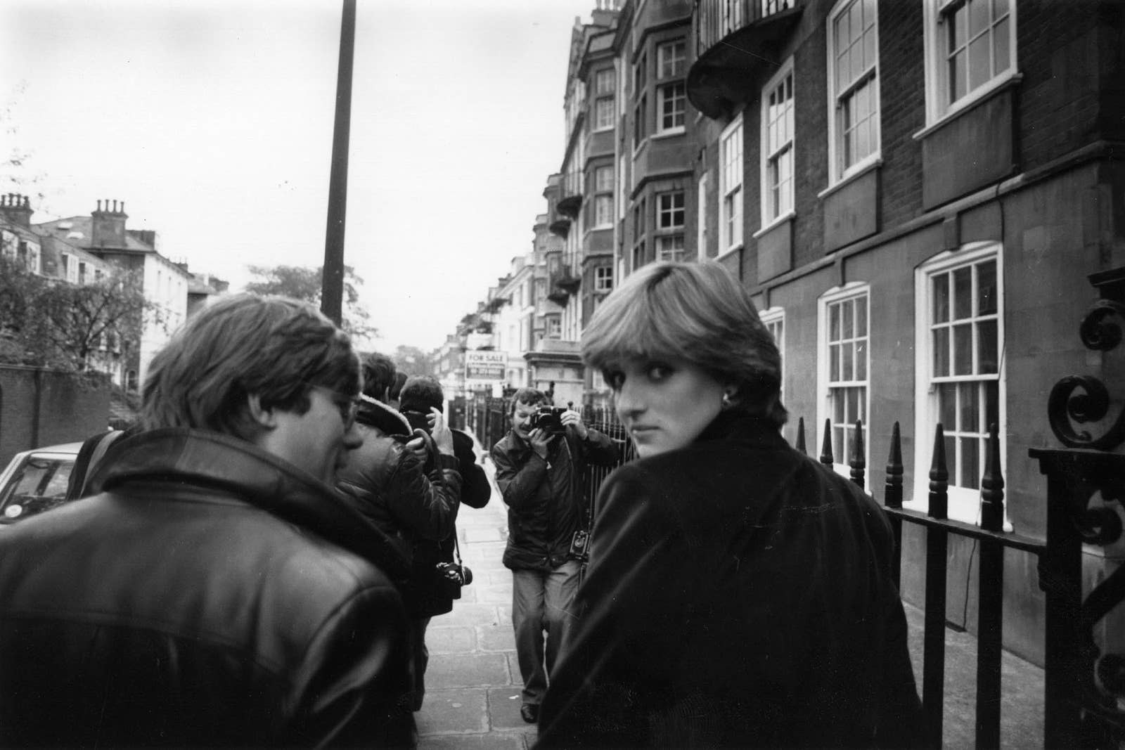 Princess Diana looking back over her shoulder in a throng of camera operators