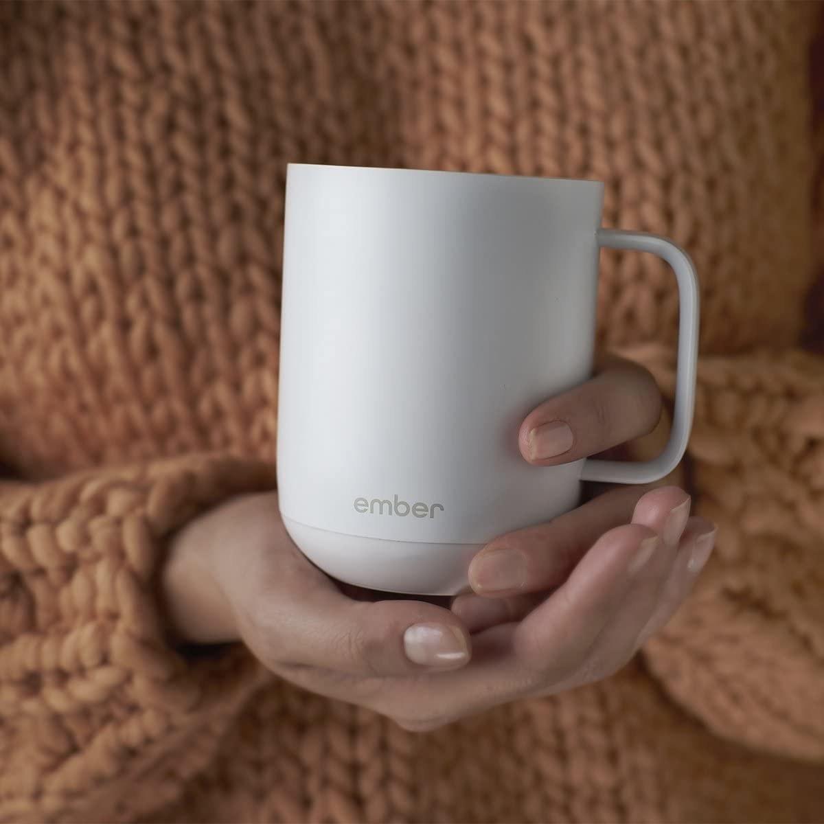 A person holding a ceramic mug