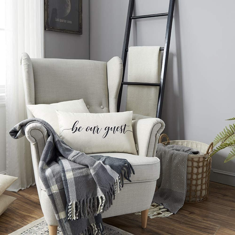 an off white throw pillow with be our guest written on it in black script lettering