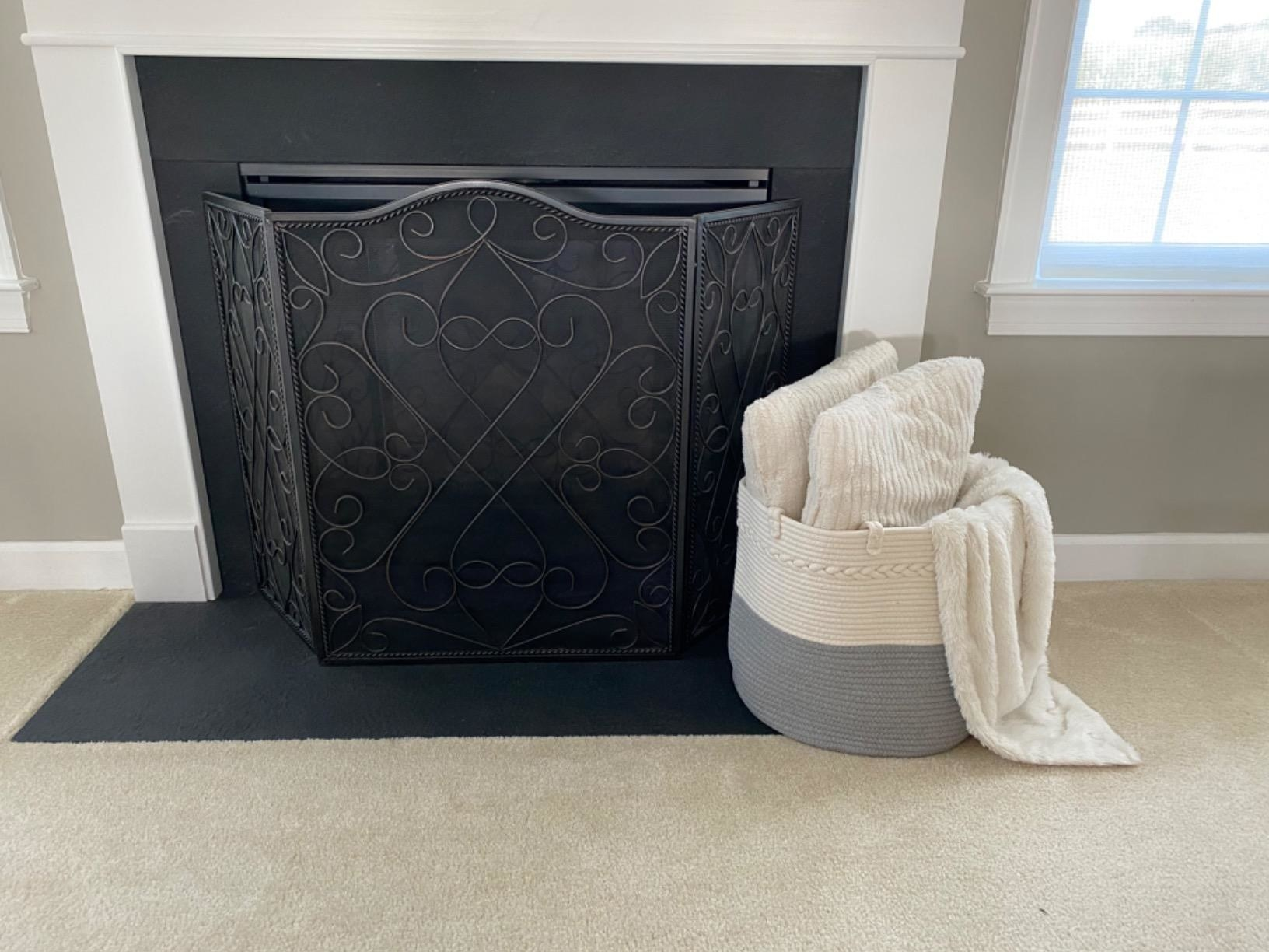 reviewer image of the mediterranean style cosyland extra large woven basket with pillows and a blanket in it propped against a fireplace