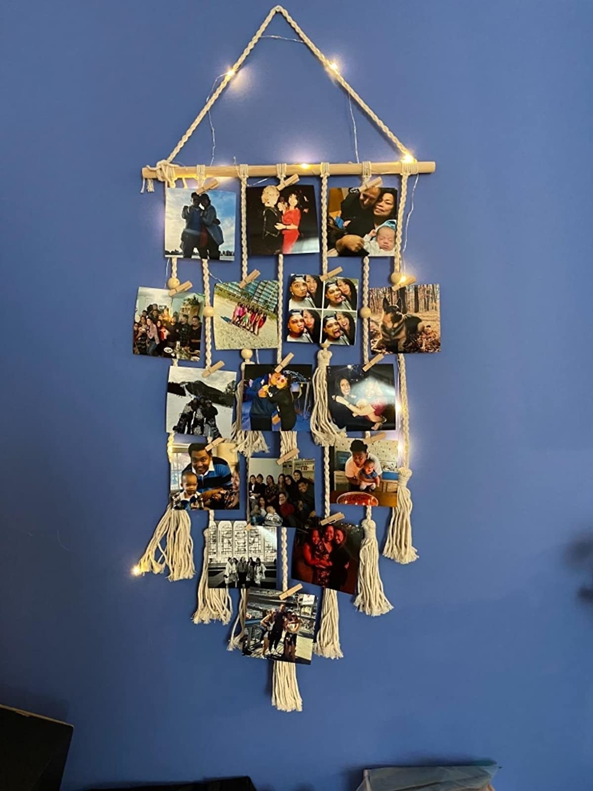 reviewer image of the Hanging macrame Photo Display on their wall with pictures clipped to it