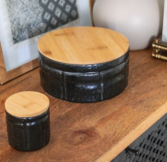 the large black canister with a wooden lid