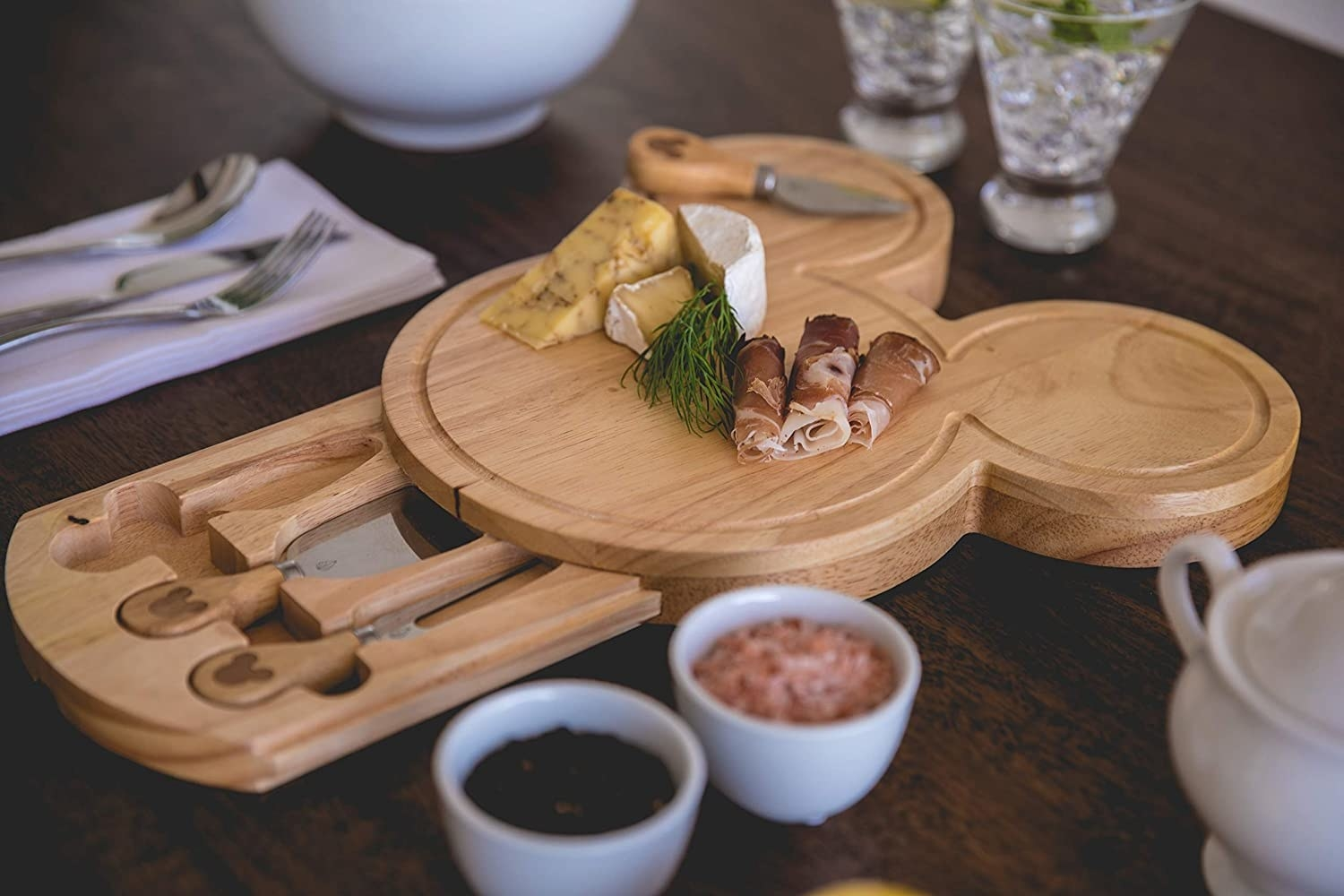 the wooden mickey-shaped cheese board with a drawer out filled with cheese knives