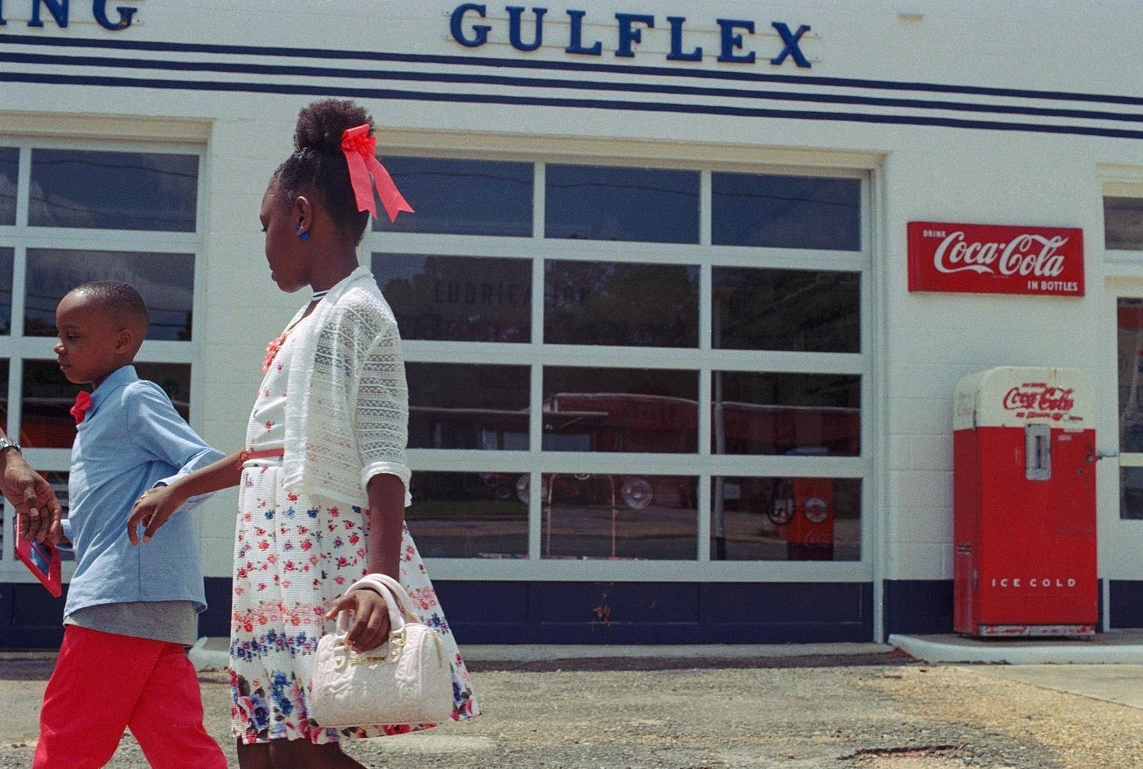 Two young children in front of a gas station
