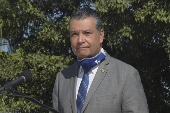 Alex Padilla stands outside, wearing a grey suit and an LA Dodgers face mask