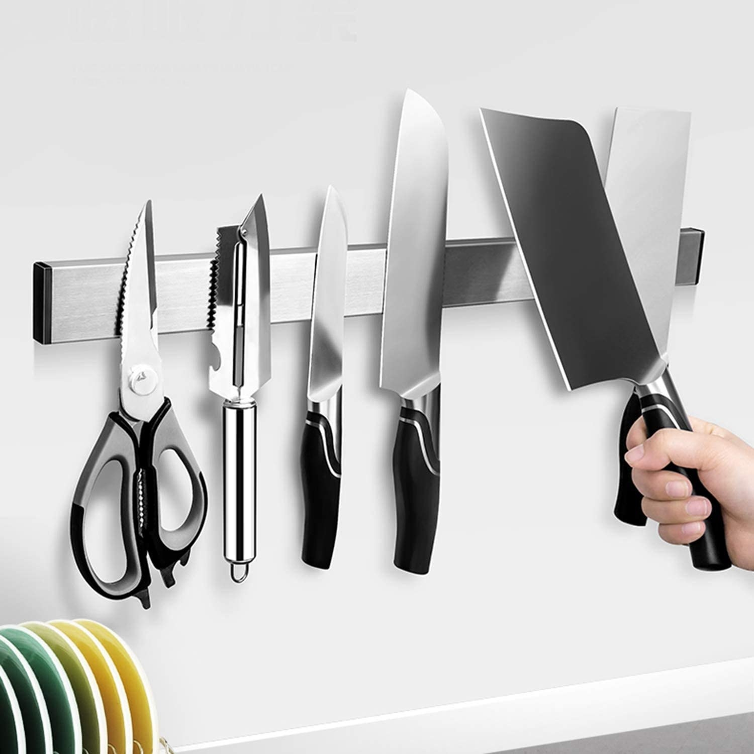 A person putting a cleaver onto a large magnetic wall strip