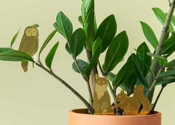 a fox, squirrel, and owl animal decoration on a plant