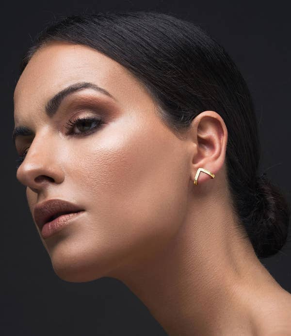 person wearing the earrings in gold