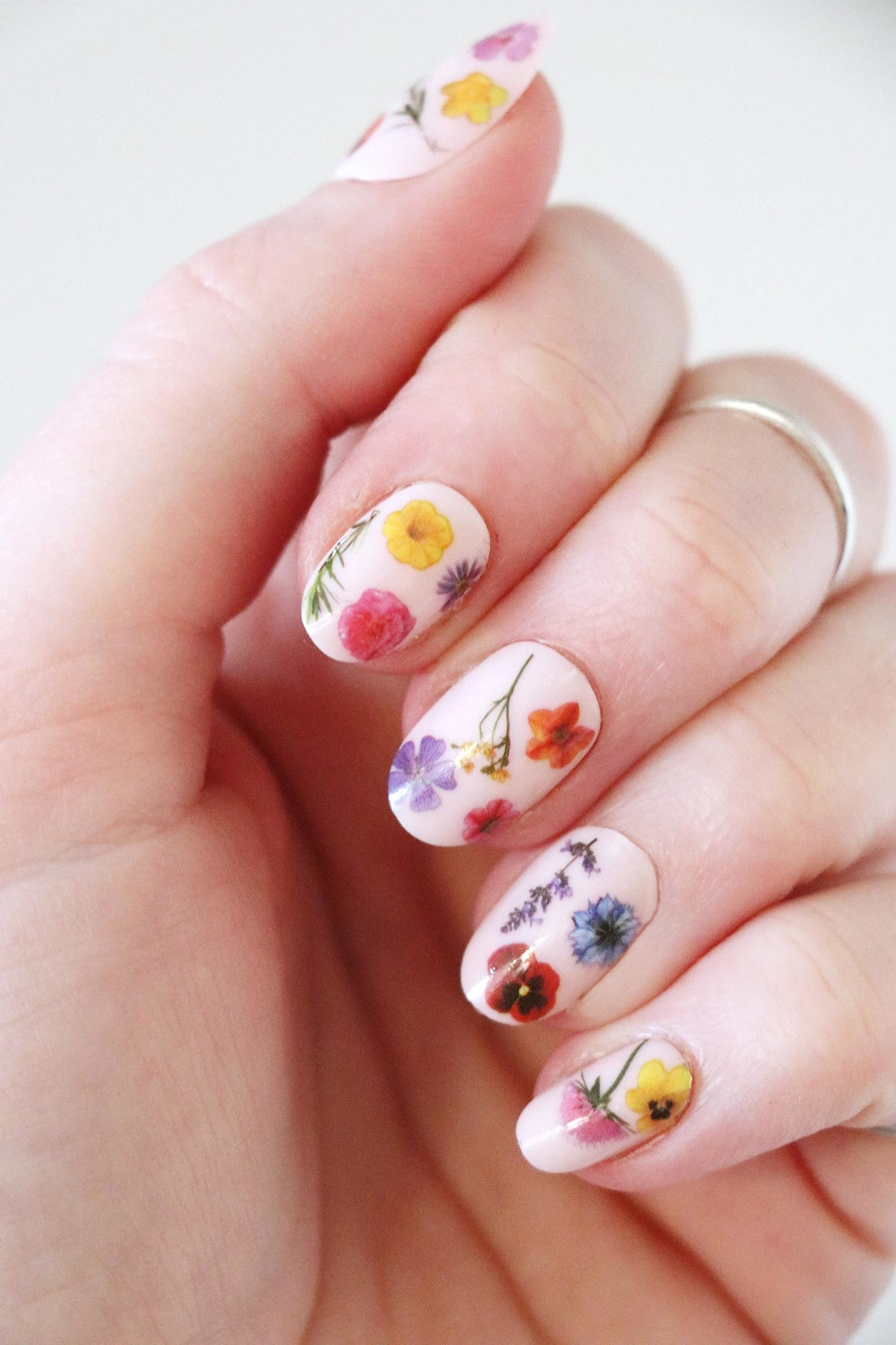 person with the floral nail tattoos on their nails