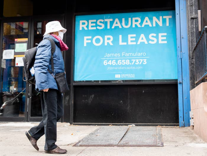 "A person walks by a sign that reads ""restaurant for lease"""