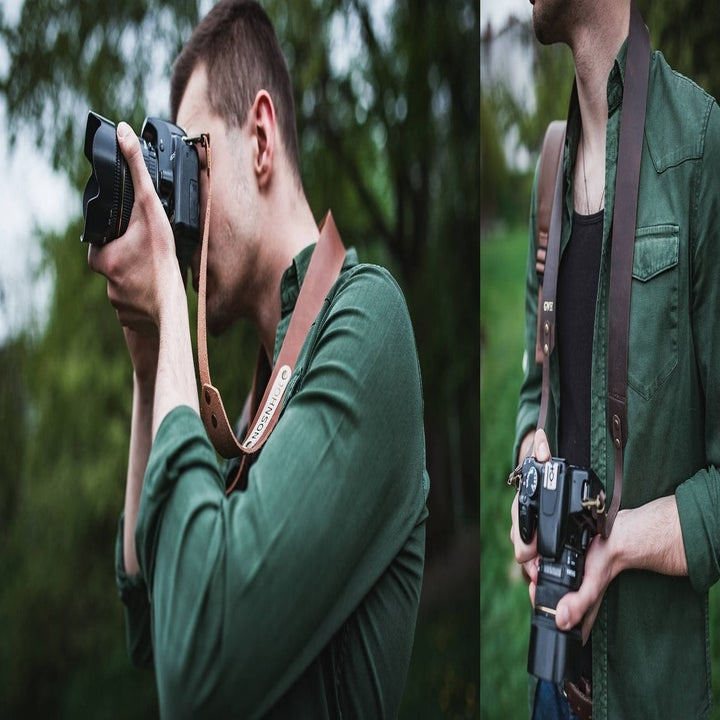 person using their camera with leather strap attached to it