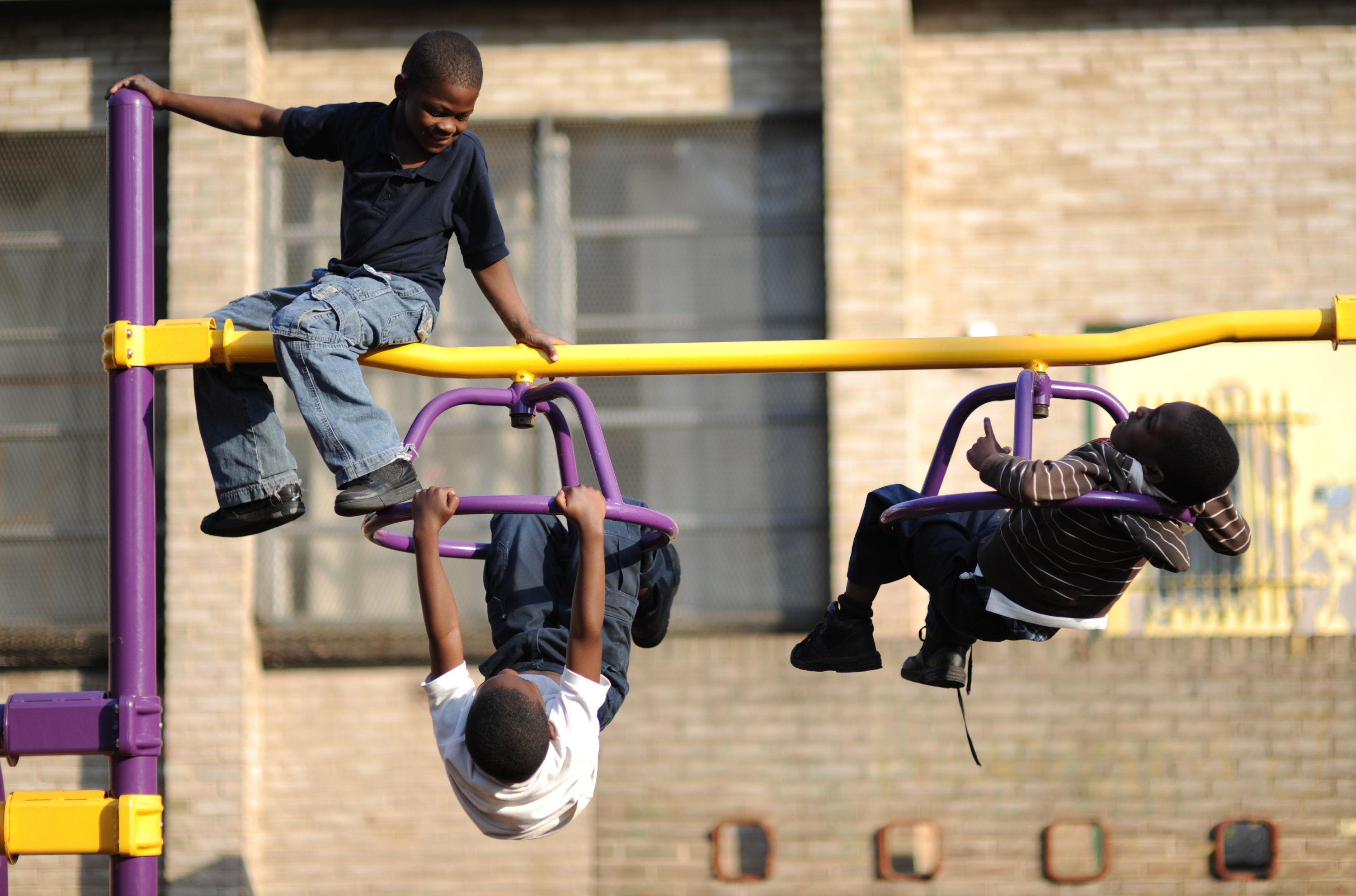 Children play on spinning monkey bars at a park
