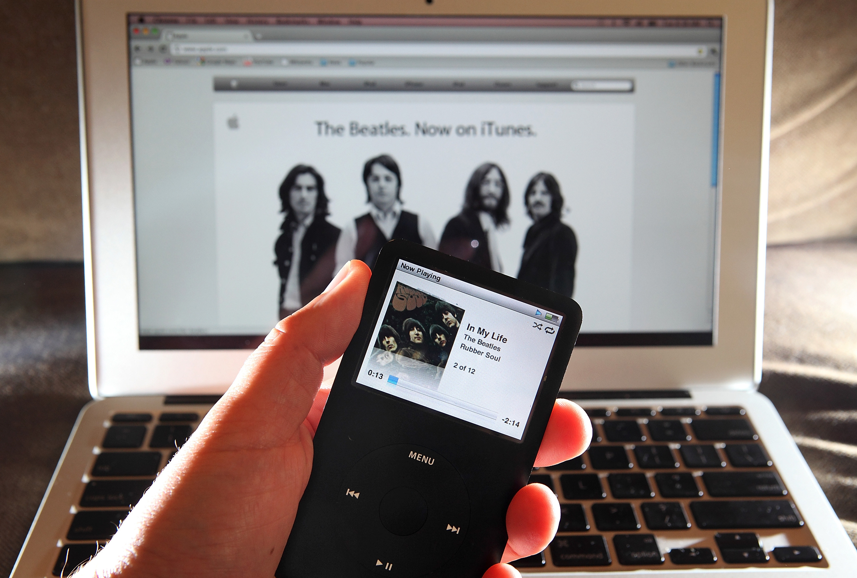 A person holds an iPod playing the Beatles in front of a Mac with iTunes open