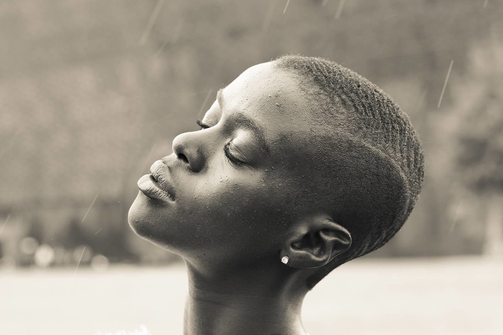 A woman with short hair stands in the rain with her head tilted back