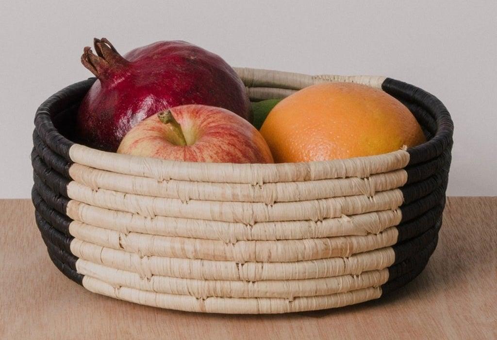 black and tan basket holding fruit