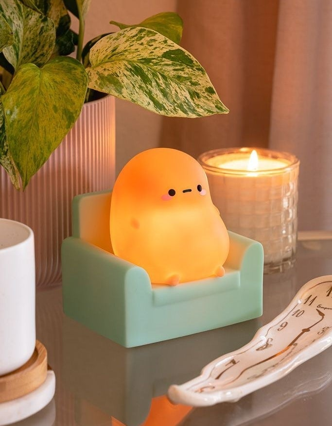 The small light shaped like a potato with a face, arms, and legs on a green armchair