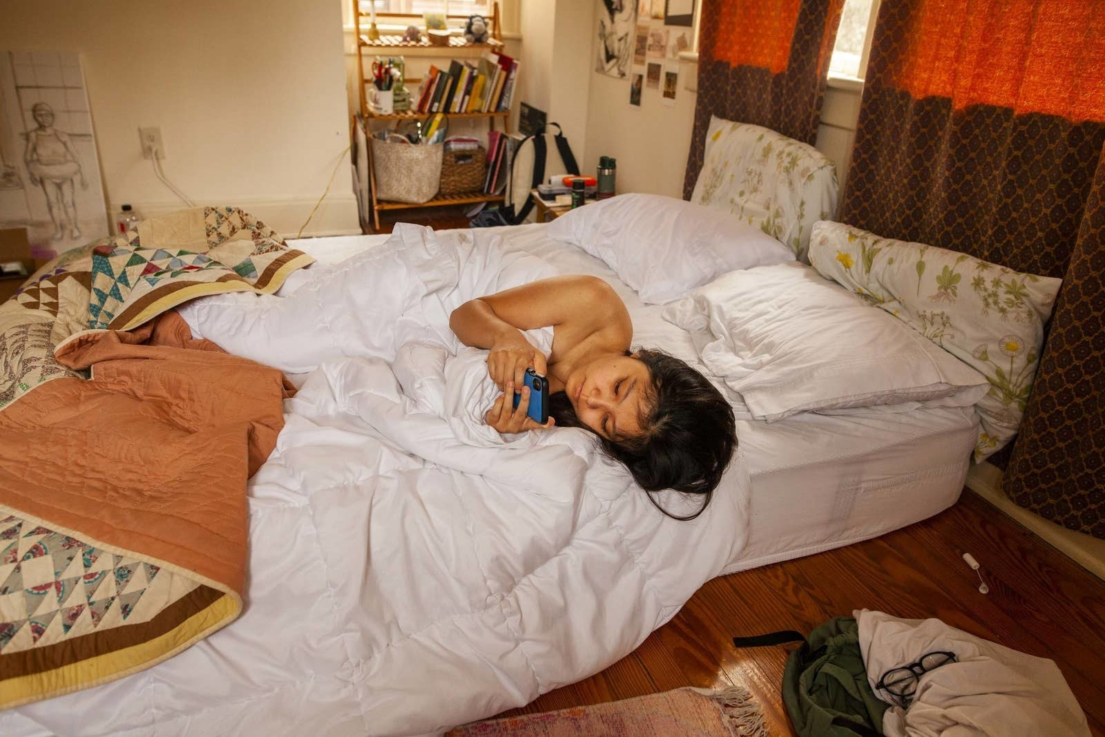 A girl is on her phone in bed, which is a mattress on the floor, with the windows drawn