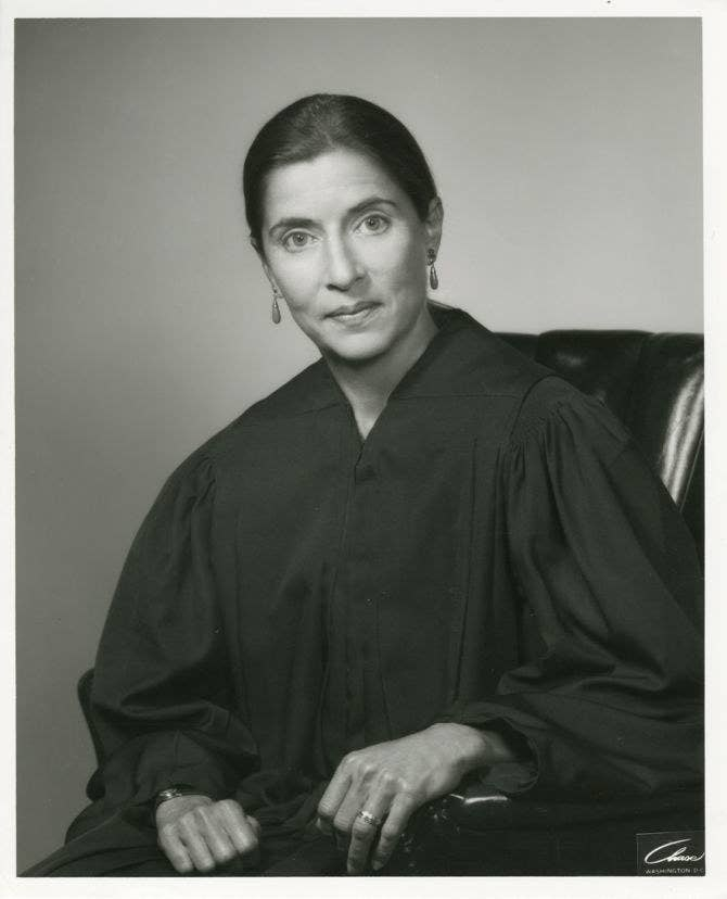An official portrait of Ginsburg, dressed in a black robe with her hair pulled back and earrings on, while she was on the US Court of Appeals for the DC Circuit